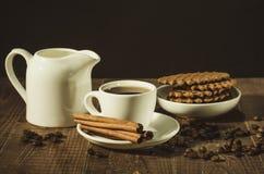 Czekoladowi opłatki, creamer, filiżanka kawy z cynamonowymi kijami, creamer i filiżanka kawy z cynamonowymi kijami,/czekoladowi o fotografia royalty free