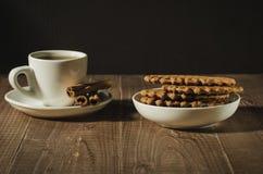 Czekoladowi opłatki, filiżanka kawy z cynamonowymi kijami i filiżanka kawy z cynamonowymi kijami na drewnianym stole/czekoladowi  obraz stock