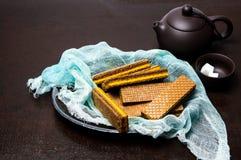 Czekoladowi opłatki na talerzu z herbacianym garnkiem zdjęcie royalty free