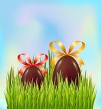 Czekoladowi Wielkanocni jajka chujący w zielonej trawie na nieba tle Kartki z pozdrowieniami dekoracji elementy z łękiem i fabork royalty ilustracja