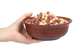 Czekoladowy śniadaniowy zboże w pucharze w ręce odizolowywającej na białych tła, brown i białych piłkach, zdrowy ranku jedzenie Fotografia Stock