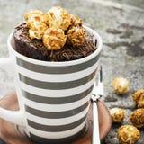 Czekoladowy aromatyczny kubka tort z karmelu apetycznym popkornem dla jesieni wygodnej ciepłej herbaty pije na szarym kamiennym t zdjęcie stock