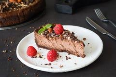 Czekoladowy cheesecake z malinkami, dokrętkami i nowym liściem na bielu talerzu, zdjęcia stock