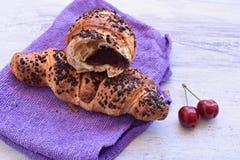 Czekoladowy croissant i wiśnie przy lekkiego drewnianego background/Śniadaniowego background/Słodkim breakfast/Zaczyna dzień obrazy royalty free