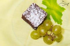 Czekoladowy gąbka tort z lodowaceń winogronami na żółtym tablecloth i cukierem Obraz Stock