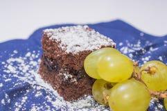 Czekoladowy gąbka tort z lodowaceń winogronami na błękitnym tablecloth i cukierem Zdjęcie Royalty Free