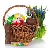 Czekoladowy królik, jajka w koszu i kwiaty, zdjęcia stock