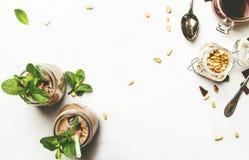 Czekoladowy milkshake, mleka koktajl z lub, zieleni nowymi i cedrowymi dokrętkami, biały kuchenny stół, kopii przestrzeń, odgórny obraz royalty free