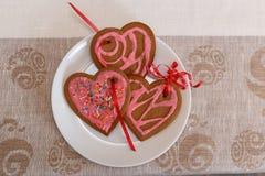 Czekoladowy piernikowy ciastka serce kształtujący z czerwieni i menchii lodowaceniem na bielu talerzu Fotografia Royalty Free