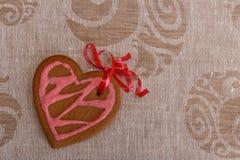 Czekoladowy piernikowy ciastka serce kształtujący z lodowaceniem i czerwieni tasiemkową następną kolorową tkaniną czerwieni i men Zdjęcie Royalty Free