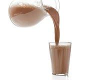 czekoladowy szkła mleka dolewanie Zdjęcia Stock