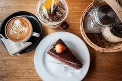 Czekoladowy tort, cappucino, brzoskwini herbata i podprawa na drewna bac, zdjęcie royalty free