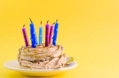 Czekoladowy tort z śmietanką i udziałami świeczki na żółtym tle zdjęcia stock