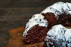 Czekoladowy tort z kwaśnymi wiśniami i wallnuts na drewnianej tnącej desce nad nieociosanym rocznika tłem, selekcyjna ostrość Zdjęcia Stock