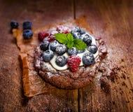 Czekoladowy tort z waniliową śmietanką i świeżymi jagodami na drewnianym stole Fotografia Royalty Free