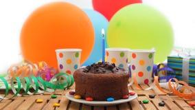 Czekoladowy urodzinowy tort z błękit świeczki paleniem na nieociosanym drewnianym stole z tłem kolorowi balony, prezenty zdjęcia royalty free