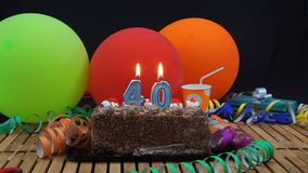 Czekoladowy urodziny 40 tort z świeczkami pali na nieociosanym drewnianym stole z tłem kolorowi balony zdjęcia stock