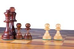 Czerń chessfamily walczy przeciw dwa białym pionkom Fotografia Stock