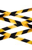 Czerń i żółta ostrożność paskowaliśmy taśmy odizolowywać Obrazy Royalty Free