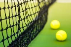 Czerń wyplatał sieć i dwa tenisowej piłki na zielonym ciężkim sądzie Zdjęcia Stock