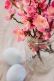 Czereśniowego okwitnięcia gałąź w szklanej słój wazie z pastelowym błękitnym Easte zdjęcia royalty free