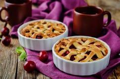 Czereśniowi kulebiaki z świeżymi wiśni oand filiżankami herbata Zdjęcie Royalty Free