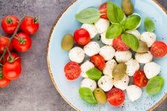 Czereśniowi pomidory, mozzarella ser, basil i pikantność na szarość łupku, drylują chalkboard Włoscy tradycyjni caprese sałatkowi zdjęcia stock