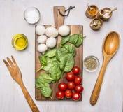 Czereśniowi pomidory, szpinak opuszczają out na ciapanie desce obok przyrządów, pieczarki, kłaść, są condiments i sałatką na drew Fotografia Stock