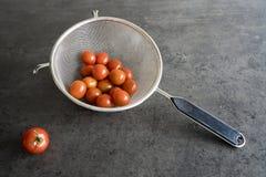 Czereśniowi pomidory w metalu durszlaku na popielatym betonowym kuchennym dresser obraz stock