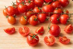 Czereśniowi pomidory - wod kropel drewna tło Zdjęcia Royalty Free
