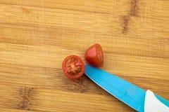Czereśniowy pomidor na drewnianej desce z błękitnym nożem Zdjęcie Royalty Free