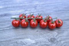 Czereśniowi pomidory na drewnianym tle Obrazy Stock
