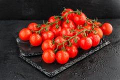 Czereśniowi pomidory na łupkowym backgound Zdjęcia Stock