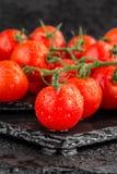 Czereśniowi pomidory na łupkowym backgound Obrazy Royalty Free