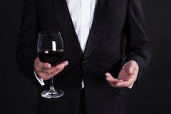 Czerep elegancki mężczyzna w eleganckim czarnym smokingu z szklaną czerwienią w zdjęcie royalty free