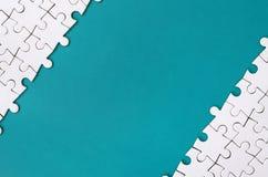 Czerep fałdowa biała wyrzynarki łamigłówka na tle błękitna klingeryt powierzchnia Tekstury fotografia z kopii przestrzenią dla te obraz stock