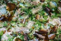 Czerepy szklanych butelek zieleń, rozrzuceni na białej powierzchni obraz stock