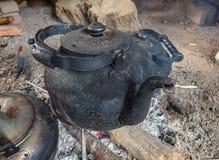 Czerniący czajnik na otwierał ogień zdjęcie royalty free