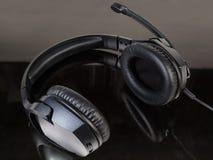 Czerni depeszującą słuchawki z pełnych rozmiarów hełmofonami na zmrok powierzchni zdjęcia stock