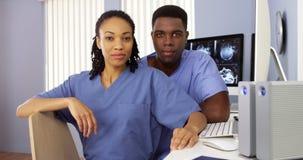 Czerni pielęgniarki w pielęgniarkach stacjonują obsiadanie przy komputerem Obrazy Royalty Free