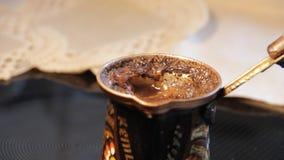 Czerni zmielona kawa warząca w miedzianym garnku na kuchence zdjęcie wideo