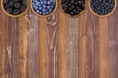 Czernicy, czarne jagody, rodzynki i czarne jagody w, drewniani puchary Zdjęcie Royalty Free