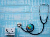 05 CZERWA blokowego kalendarza drewniana kula ziemska i stetoskop na błękitnym drewnie Obraz Stock