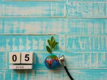 05 CZERWA blokowego kalendarza drewniana kula ziemska i stetoskop na błękitnym drewnie Zdjęcia Royalty Free