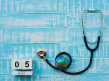 05 CZERWA blokowego kalendarza drewniana kula ziemska i stetoskop na błękitnym drewnie Zdjęcia Stock