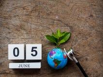 05 CZERWA drewniany kalendarzowy blok, kula ziemska i stetoskop na drewnianym t, Obrazy Royalty Free