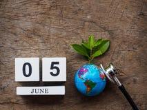 05 CZERWA drewniany kalendarzowy blok, kula ziemska i stetoskop na drewnianym t, Zdjęcia Royalty Free