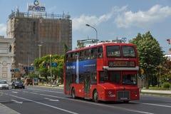 Czerwień autobusu piętrowego autobusu omijanie przez ulic miasto Skopje, republika Obraz Stock