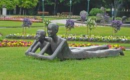 Czerwiec 6, 2011, Austria, Jeziorny Wolfgang sąsiedztwo: Rzeźbiona grupa przedstawia dwa mężczyzn mężczyzna i kobieta kłam fotografia stock