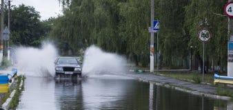 Czerwiec 21, Vyshenky Ukraina Konsekwencje prysznic Samochód bryzga przez wielkiej kałuży na zalewającej ulicie Obraz Royalty Free